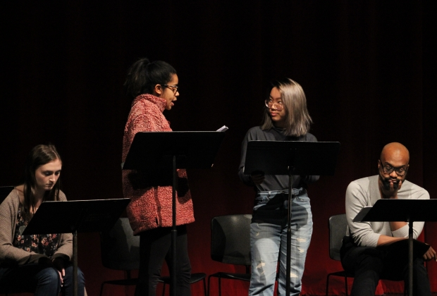 Two people on stage behind music stands, reading off scripts to each other. Two people sit in the background waiting to read.