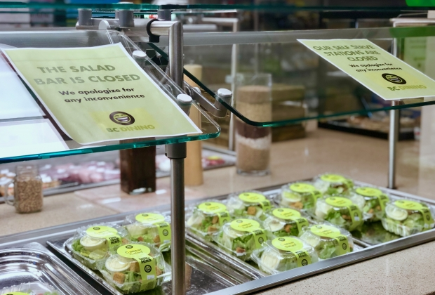 Photo taken of dining hall at Boston College, with signs warning of the virus, food wrapped in plastic.