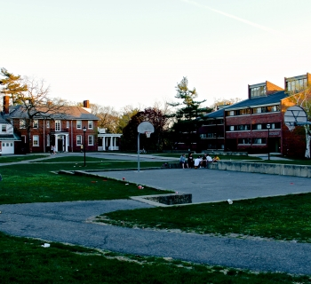 The basketball court on upper campus, backed by medieros hall and shaw house at sunset. A group of friends sits on the ledge, talking.