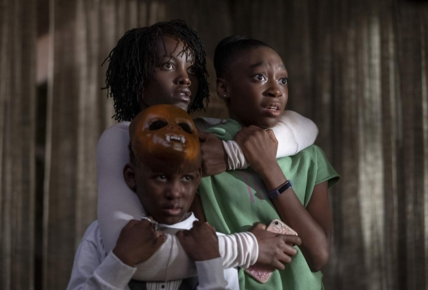 family hugging, frightened look. Boy has a mask on top of his head.