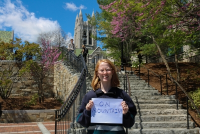 "Caroline standing on the million dollar stairs, gasson in the background, with an ""on mountains"" sign."