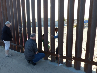 Man speaking to kids through the border wall