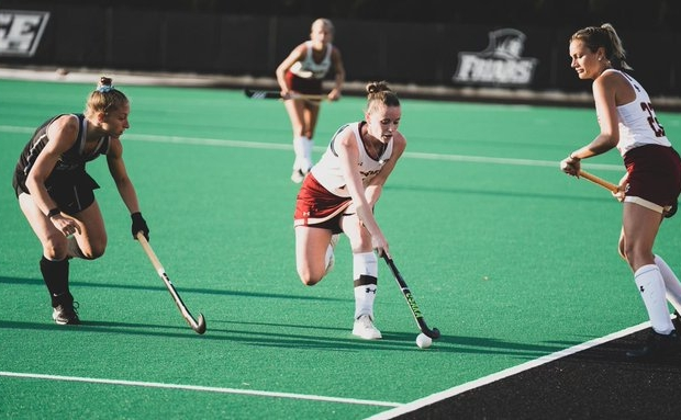 bc field hockey player surrounded by opposing team, hitting the ball with her stick.