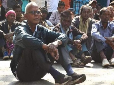 Father Swamy sitting on the ground, with other people sitting behind him and watching.