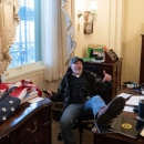 Trump-Supporter sitting in a chair in the Capitol after infiltrating with other pro-Trump members.